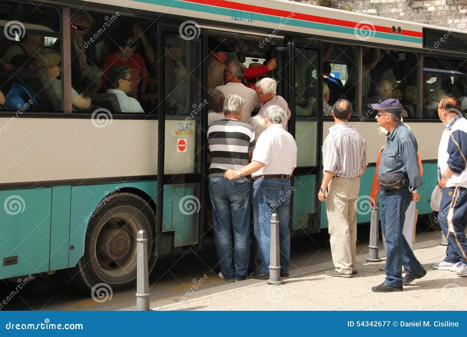 Люди всходя на борт переполненной шины разделение Хорватия