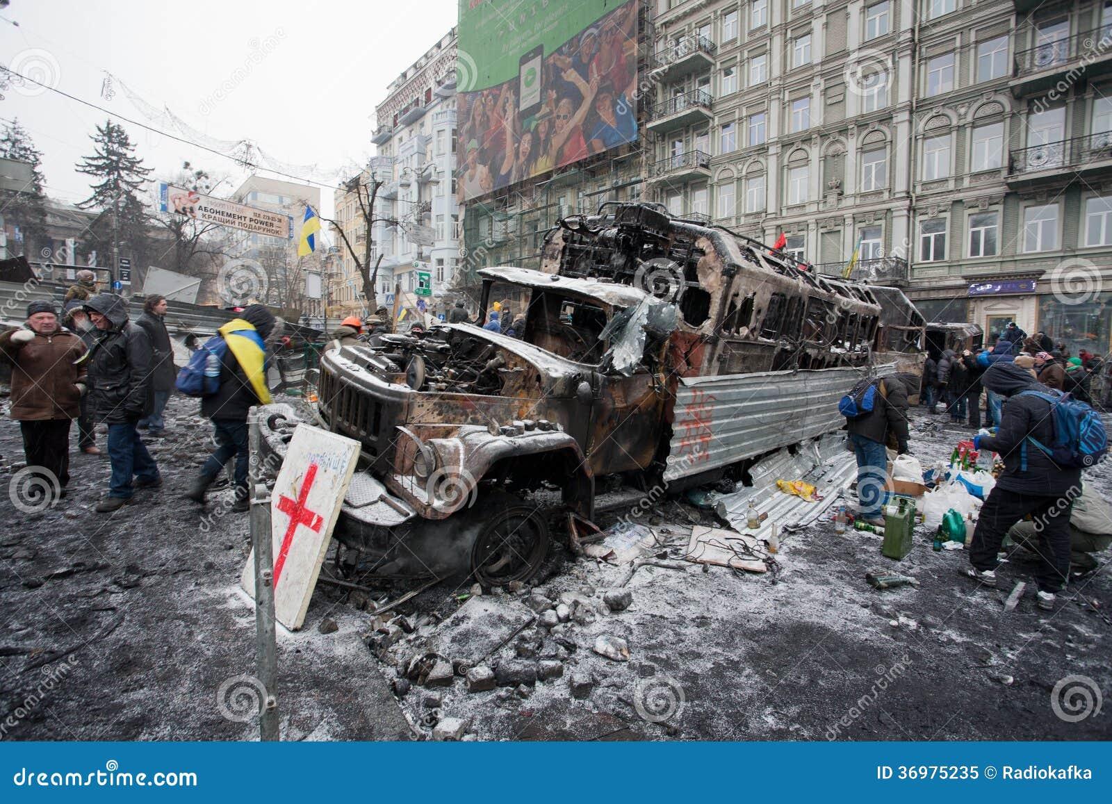 Люди идут вокруг баррикад с автомобилями ожога вне воинскими на улице снега во время антипровительственного протеста