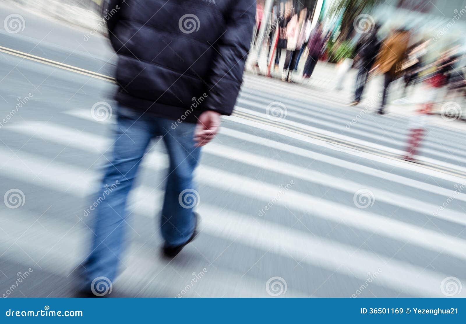 Люди идя на большую улицу города
