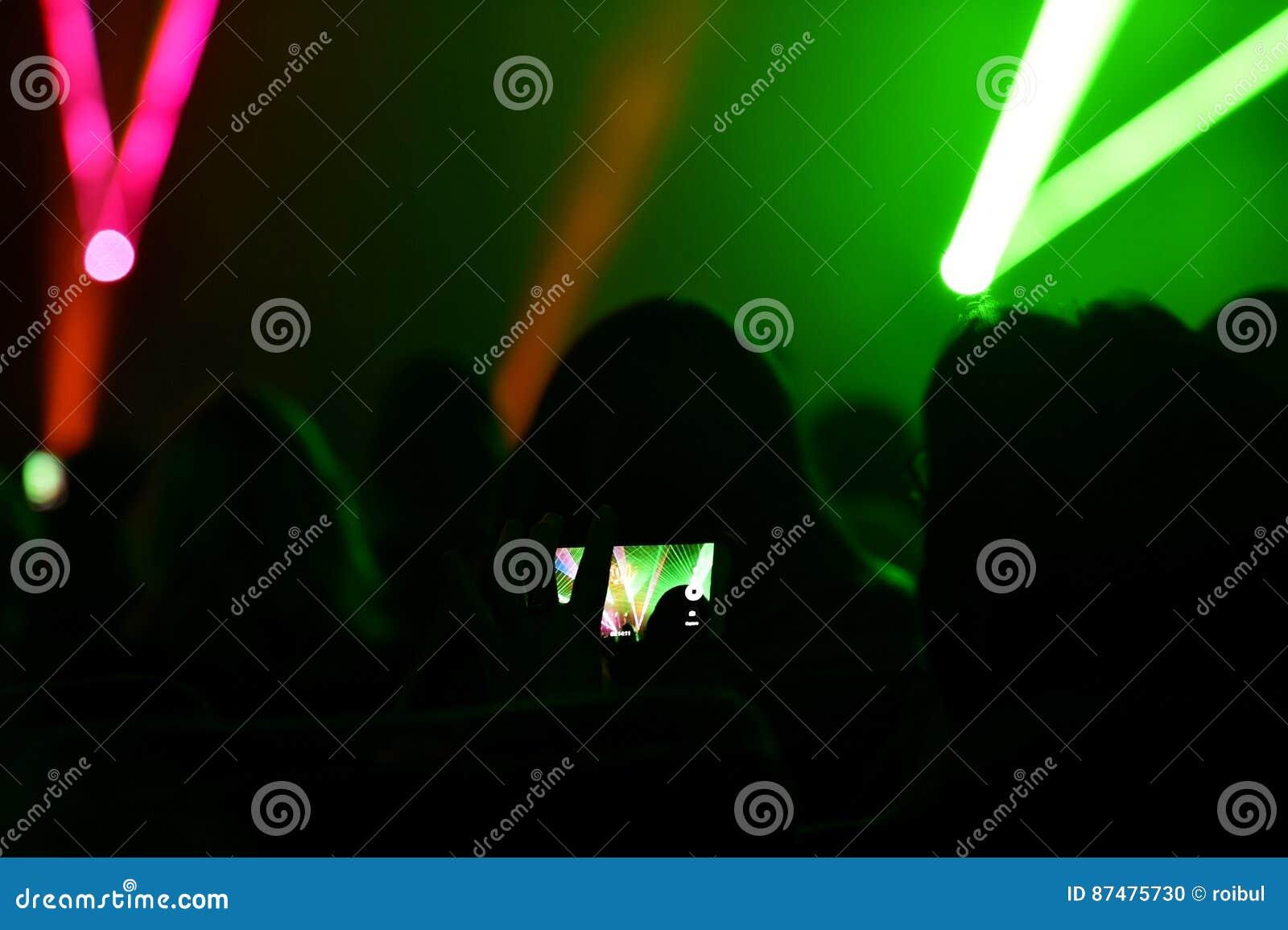 Люди наблюдая, как лазер показал