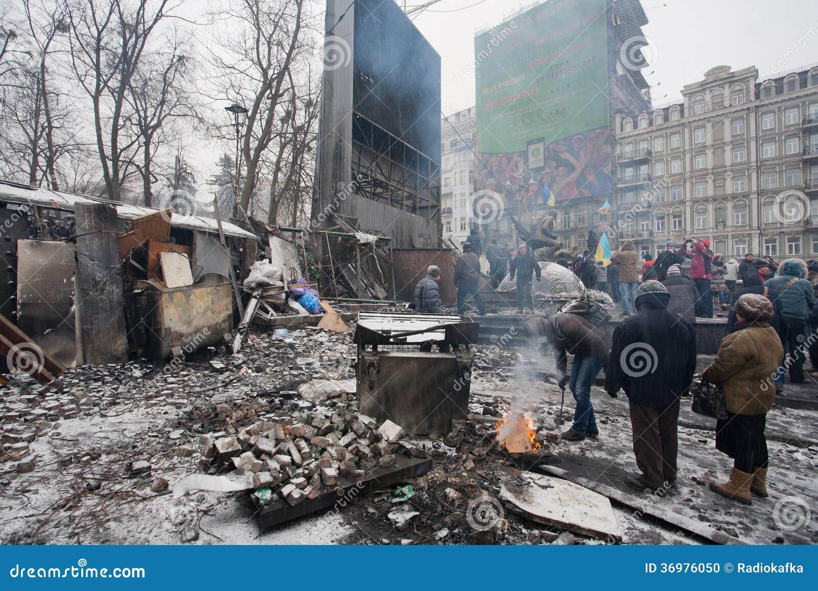 Люди нагревая огнем около баррикад после боев с полицией на сломленной улице Киева во время антипровительственного бунта