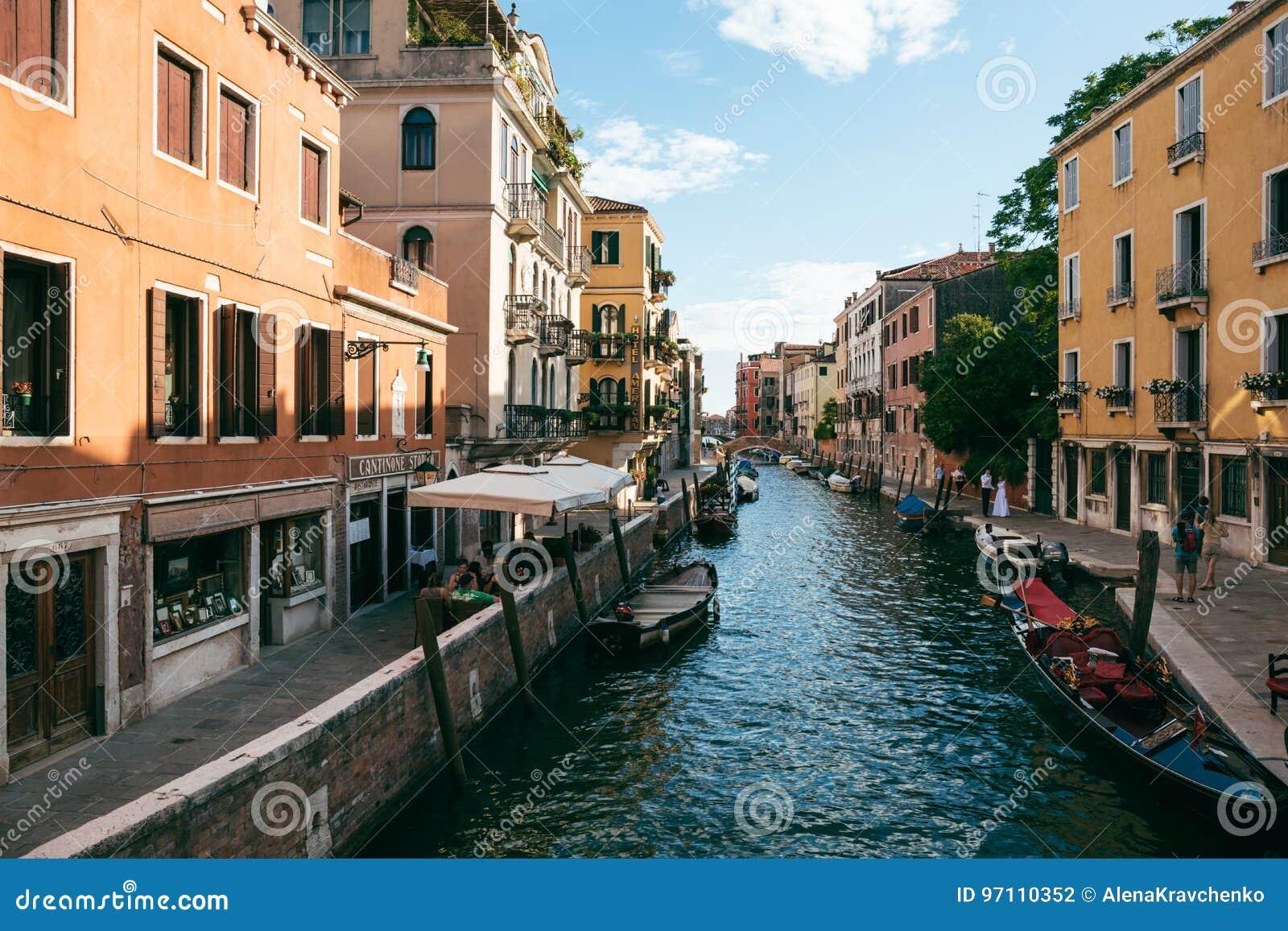 Люди наряду с каналом в Венеции на солнечный летний день