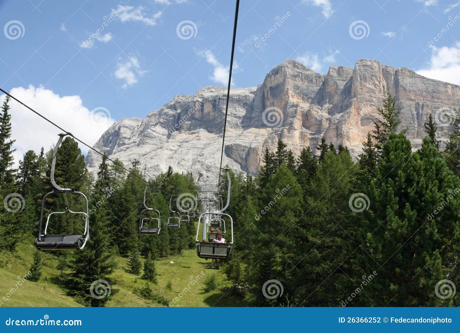 Люди подъема стула вверх к верхней части доломитов