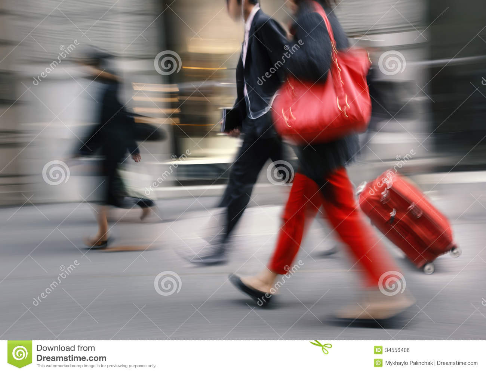 Люди с красной сумкой и чемоданом идя вниз с улицы