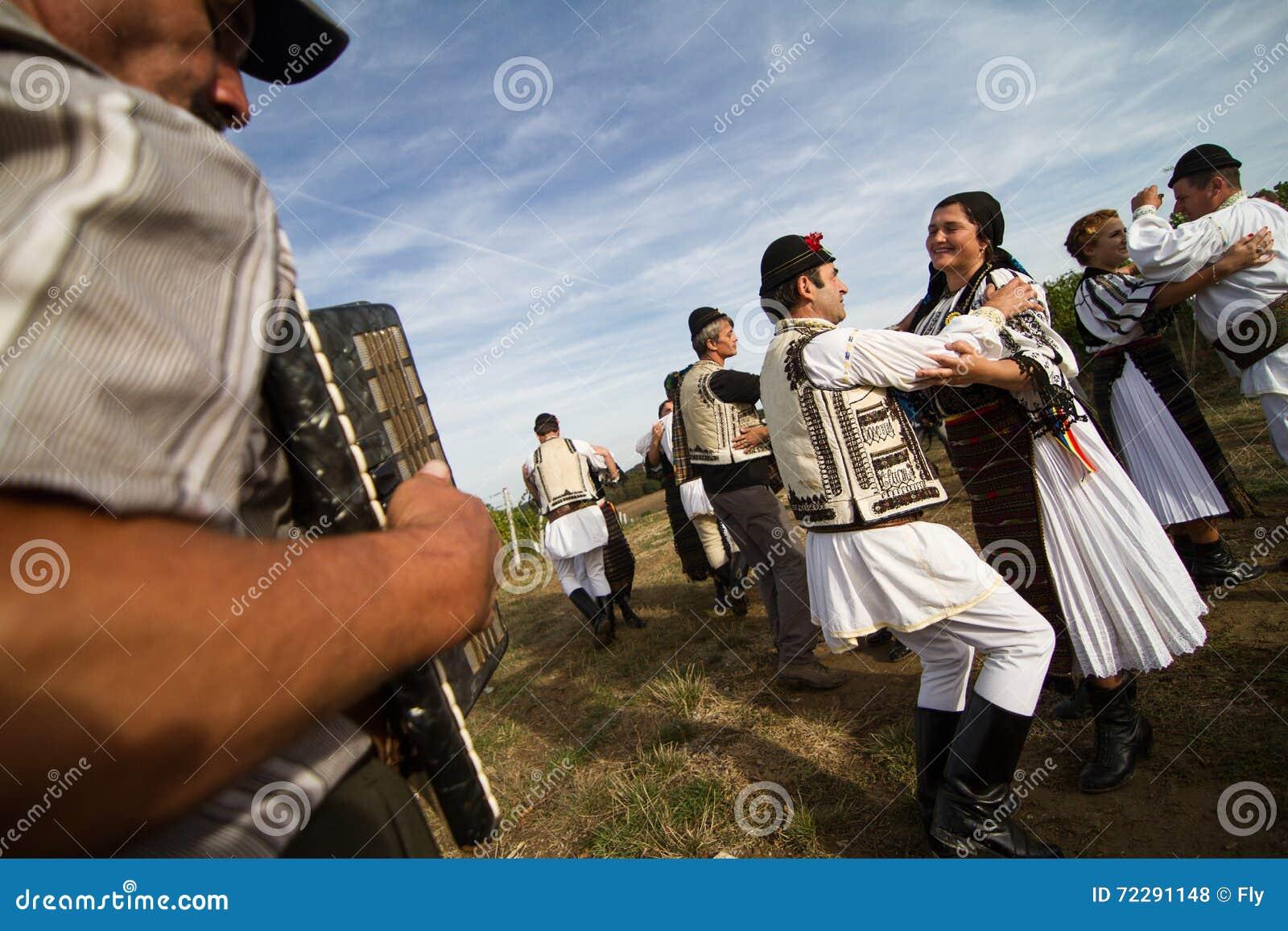 Люди танцуя на традиционном винограднике Jidvei жмут справедливо