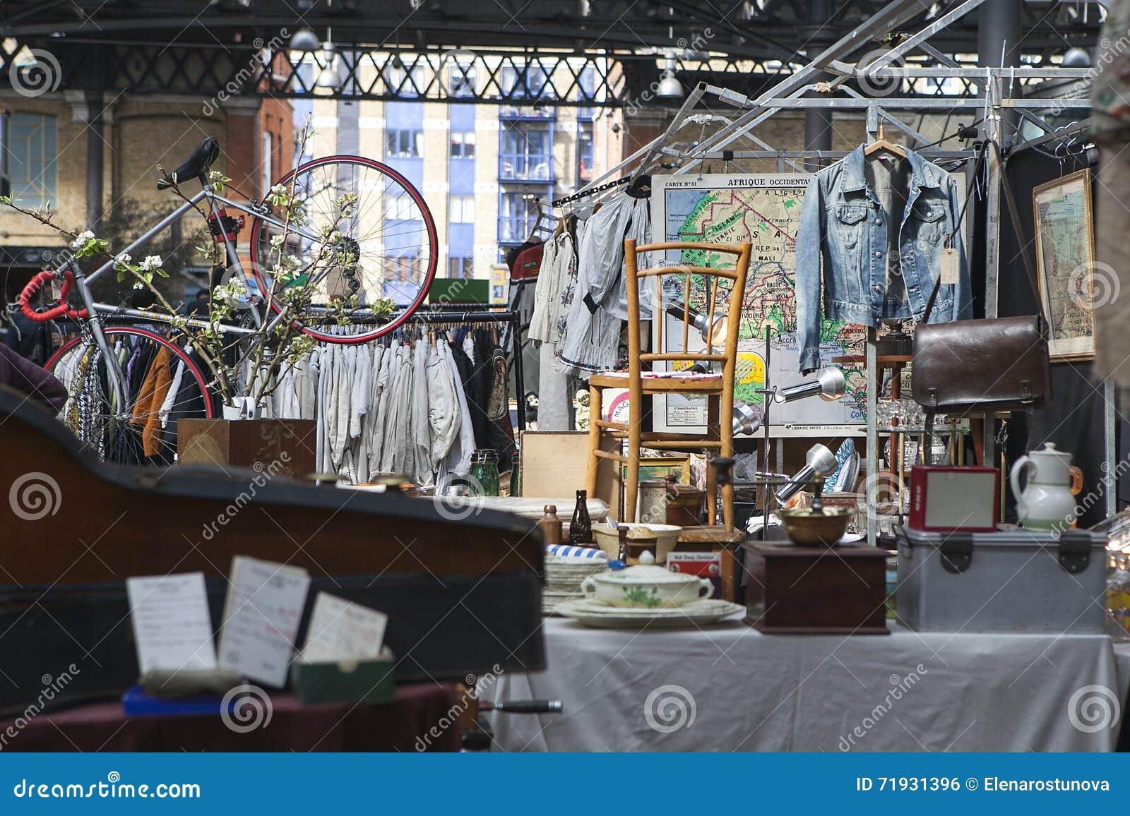 Люди ходят по магазинам на старом рынке Spitalfields в Лондоне Рынок существует