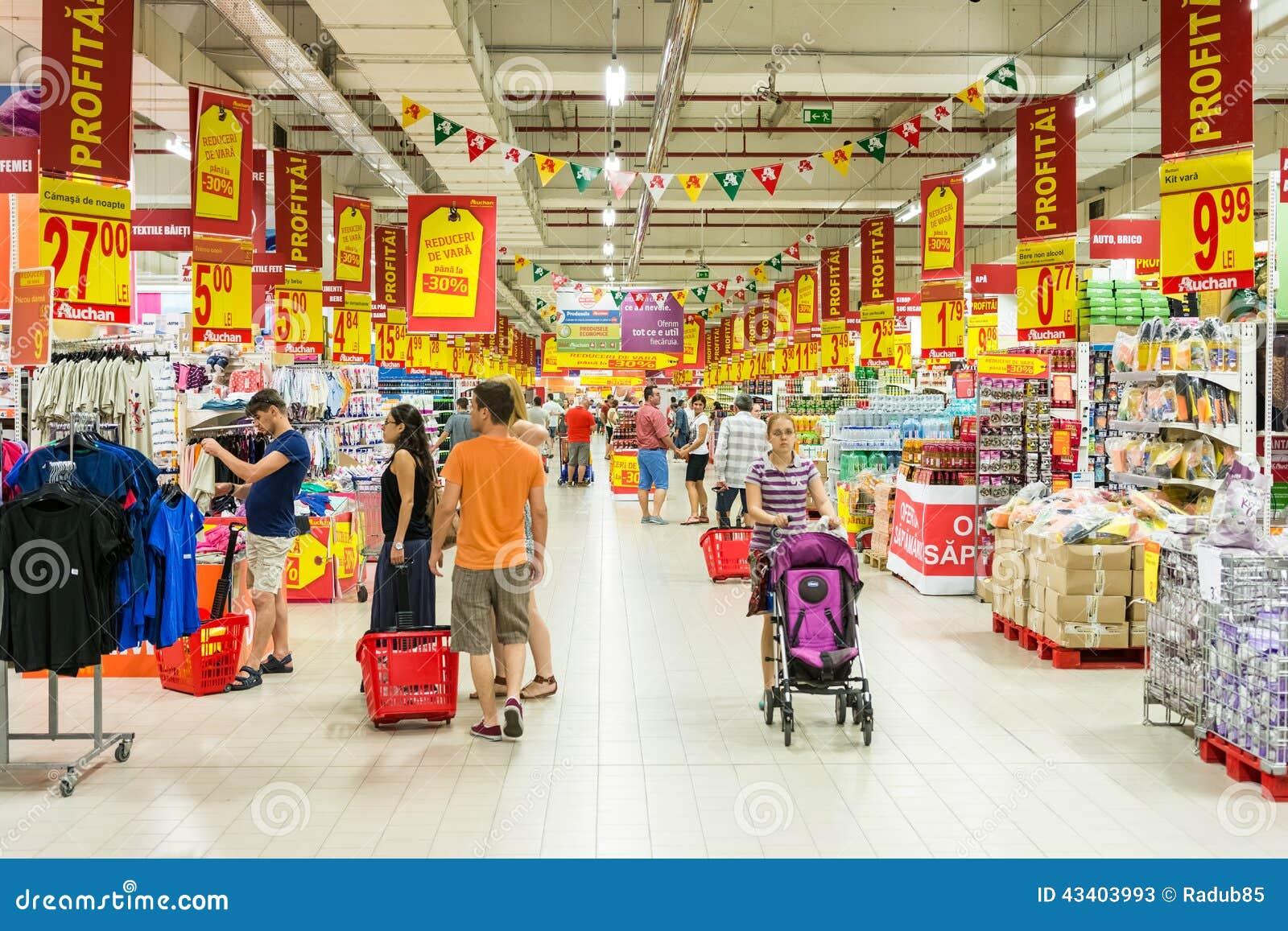 Люди ходя по магазинам в междурядье магазина супермаркета