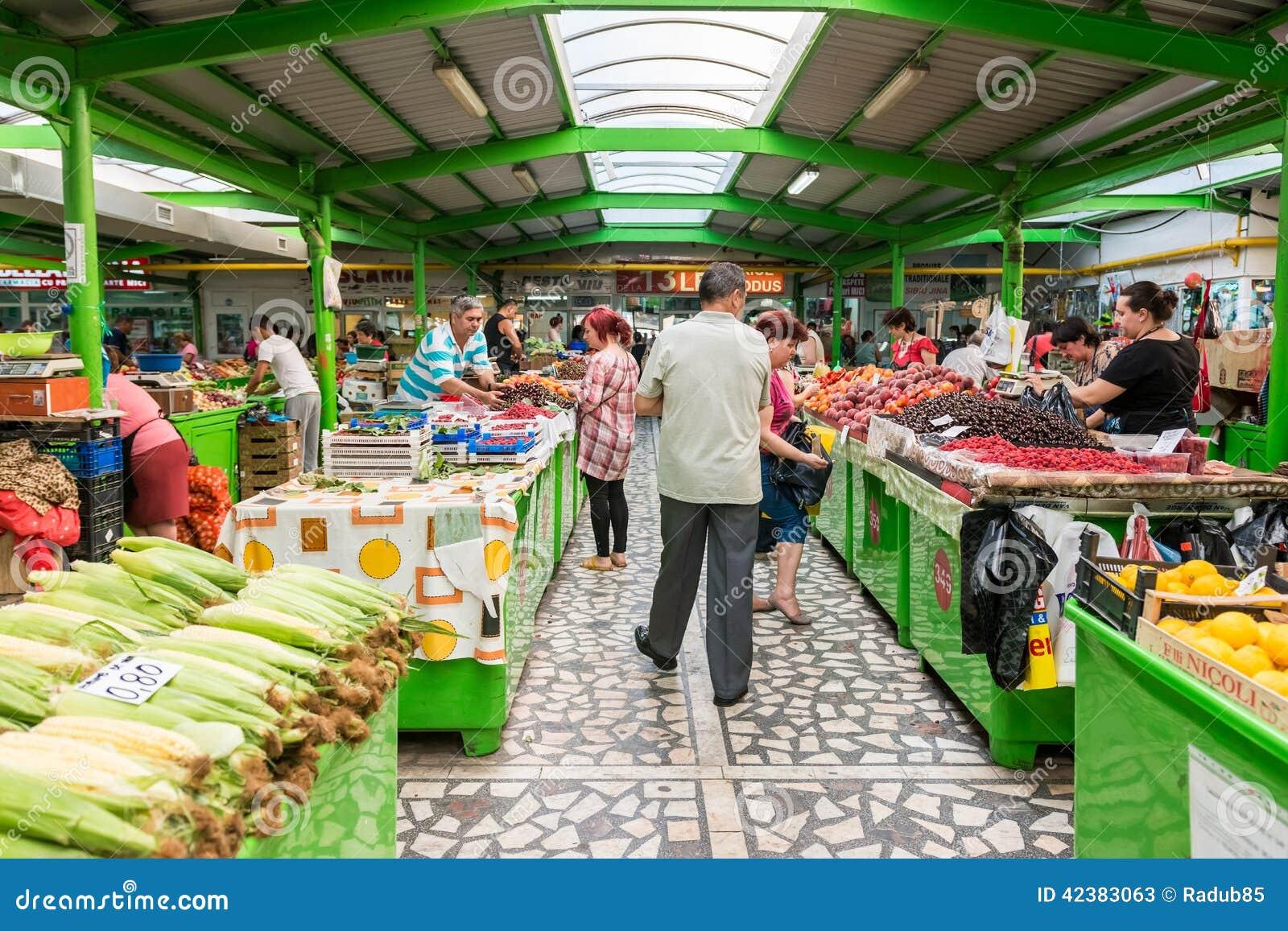 Люди ходя по магазинам для фруктов и овощей