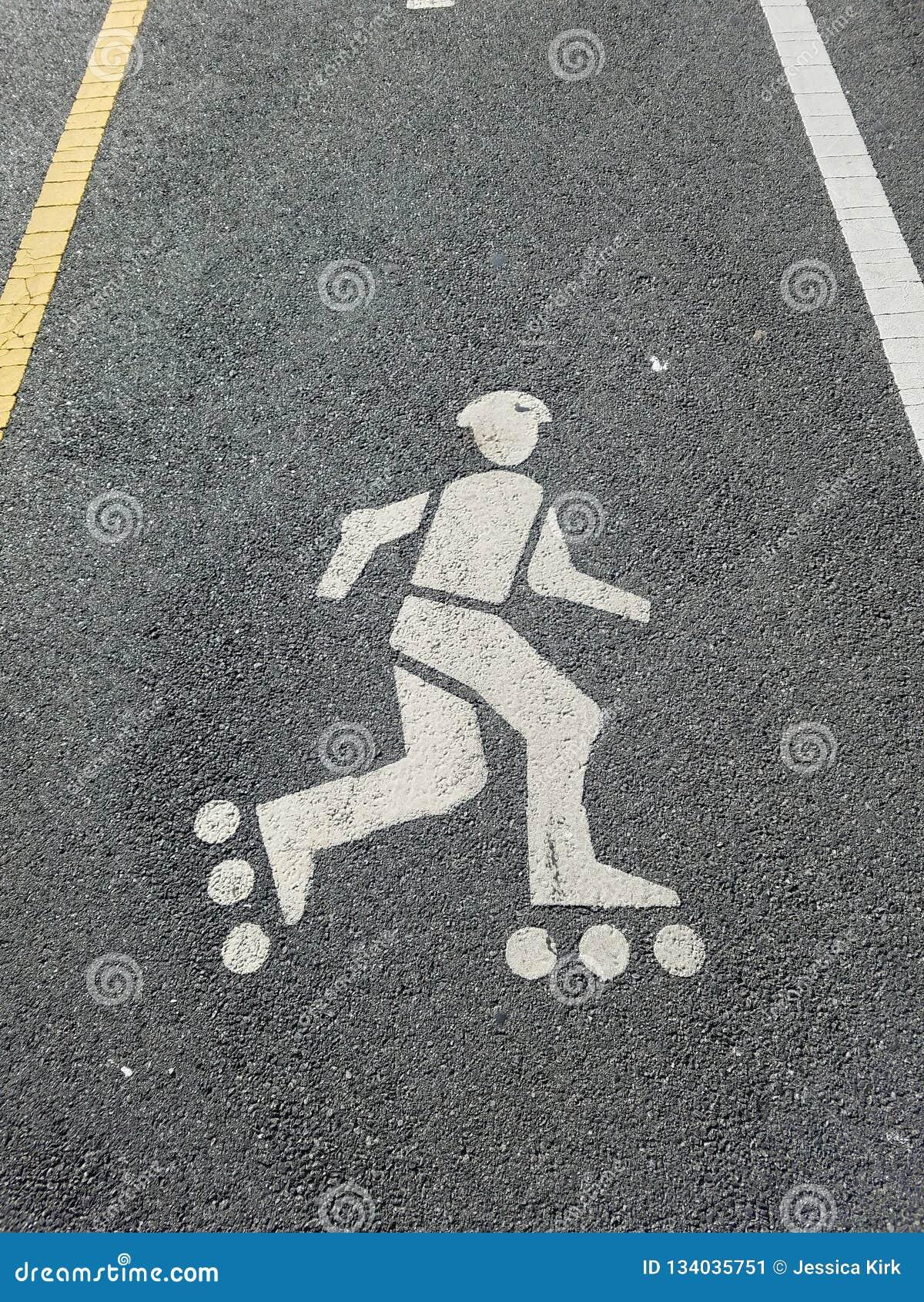 Майна кататься на коньках ролика на пути велосипеда, с желтыми и белыми линиями раздела