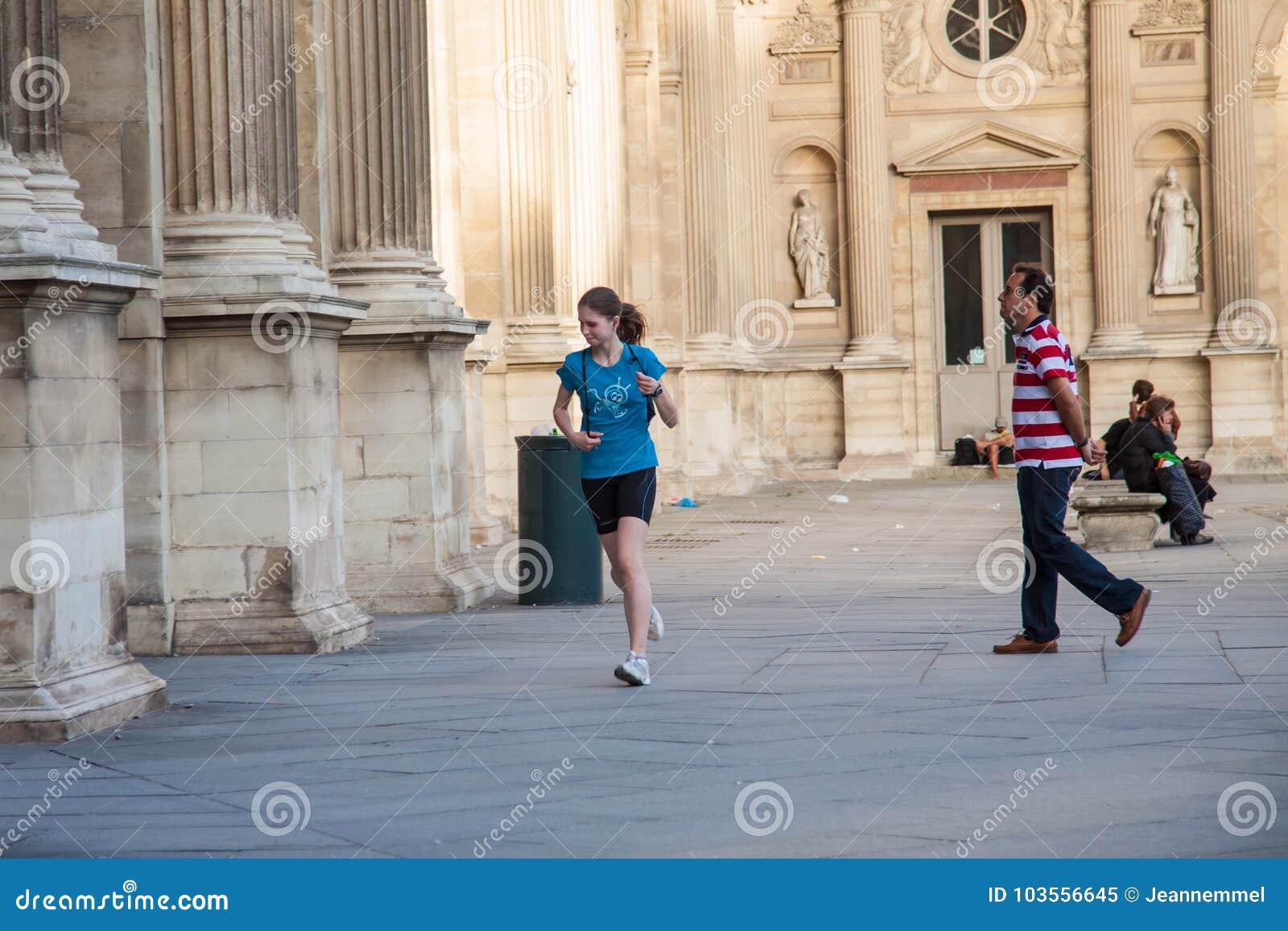 Маленькая девочка бежать вдоль стен Лувра