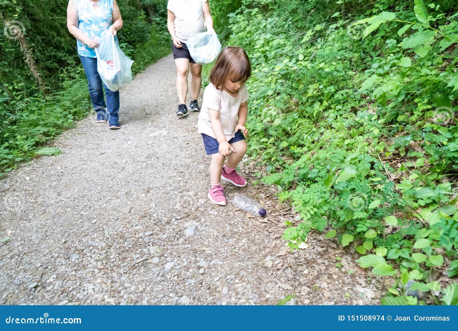 Маленькая девочка, беременная мать и бабушка очищая лес пластмасс