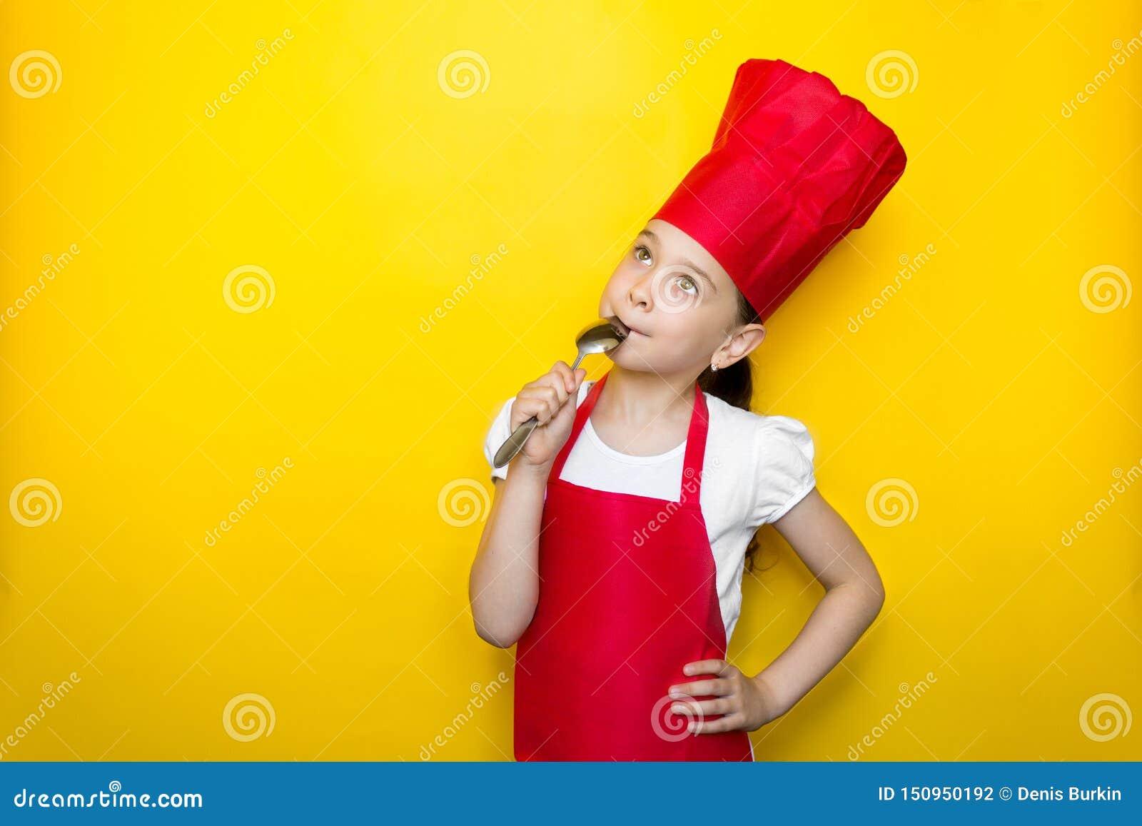 Маленькая девочка в костюме красного шеф-повара лижет ложку, мечты, очень вкусный вкус, на желтой предпосылке с космосом экземпля
