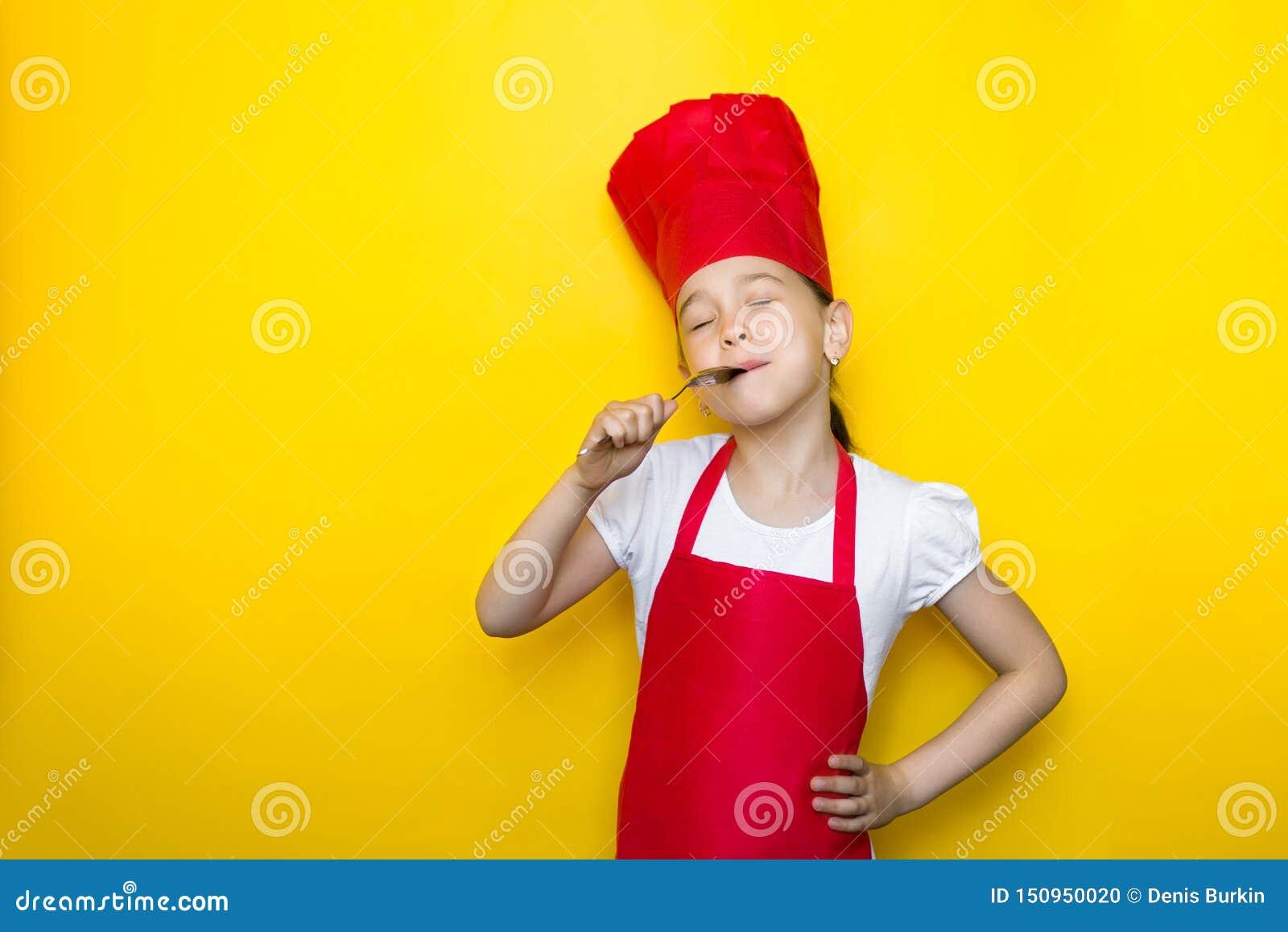 Маленькая девочка в костюме шеф-повара лижет ложку, закрывая ее глаза, очень вкусный вкус, на желтой предпосылке с космосом экзем