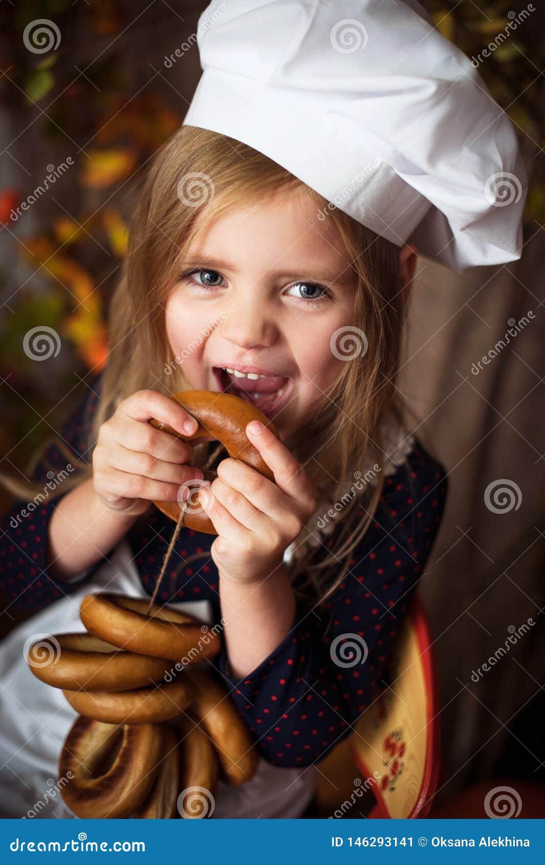 Маленькая девочка в одеждах повара с бейгл в ее руках и усмехаться