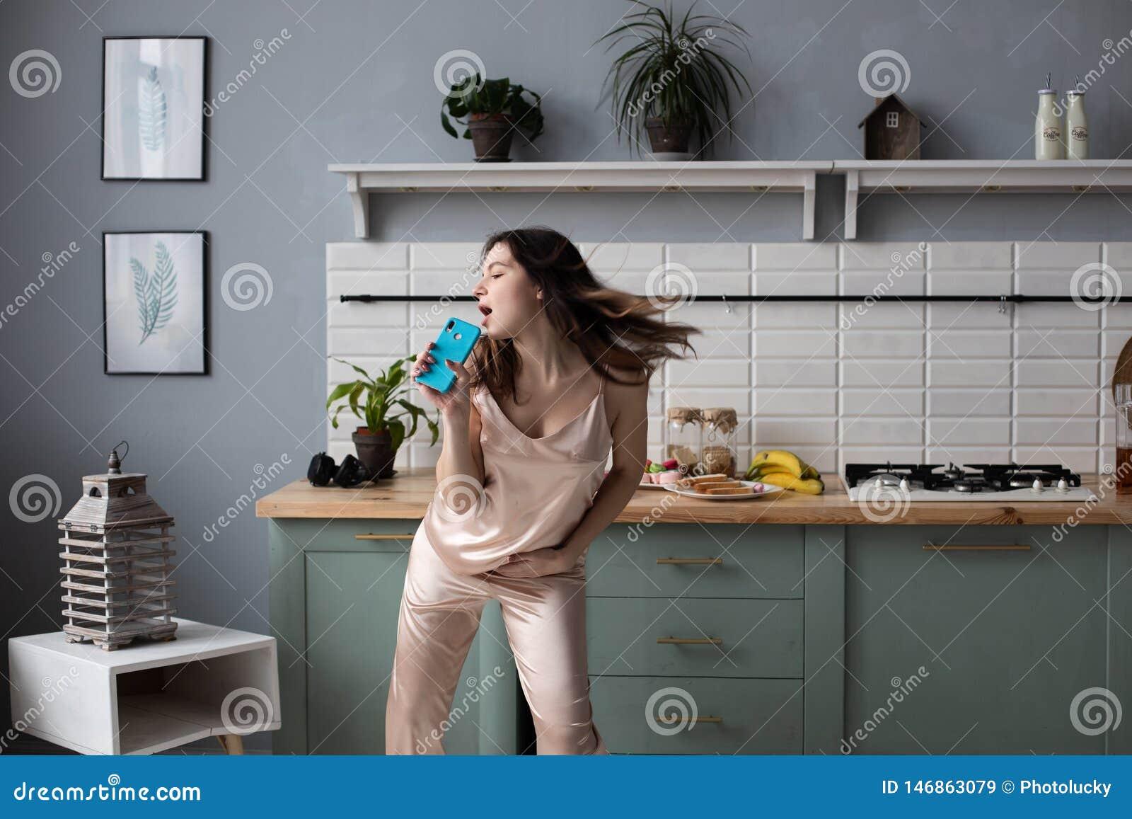 Маленькая девочка в пижамах танцуя в утре на кухне