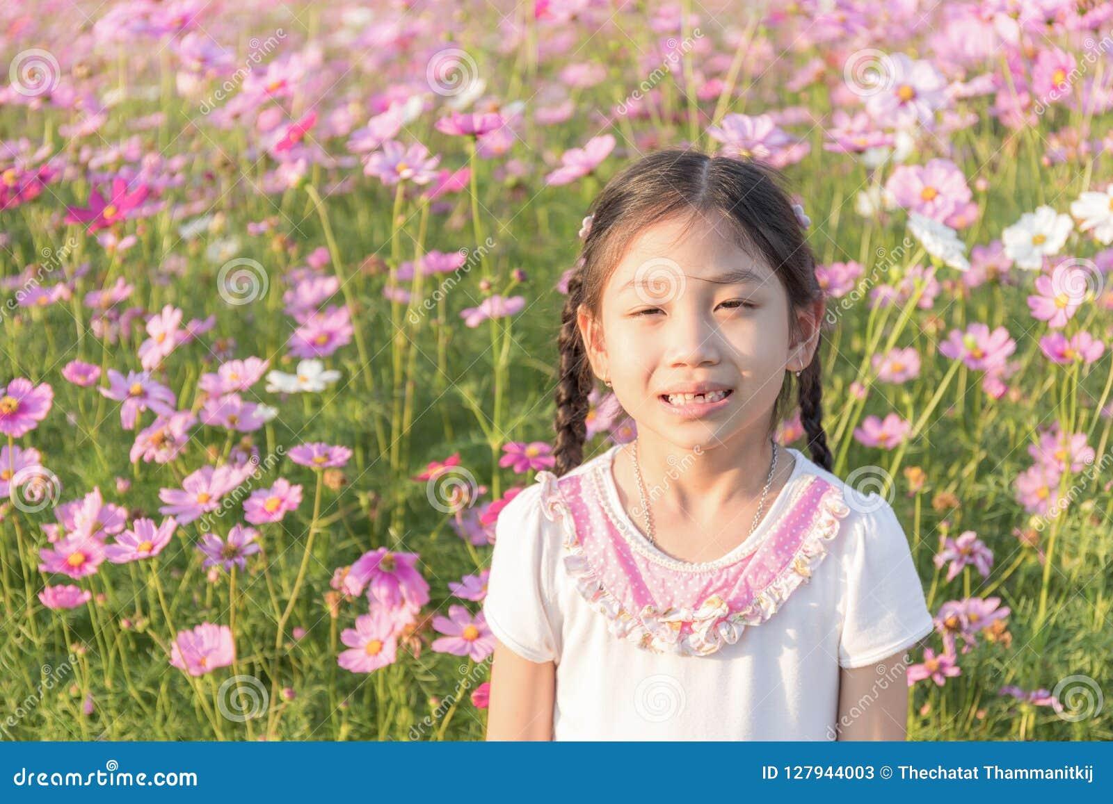 Маленькая девочка в поле розового космоса Bipin цветка космоса