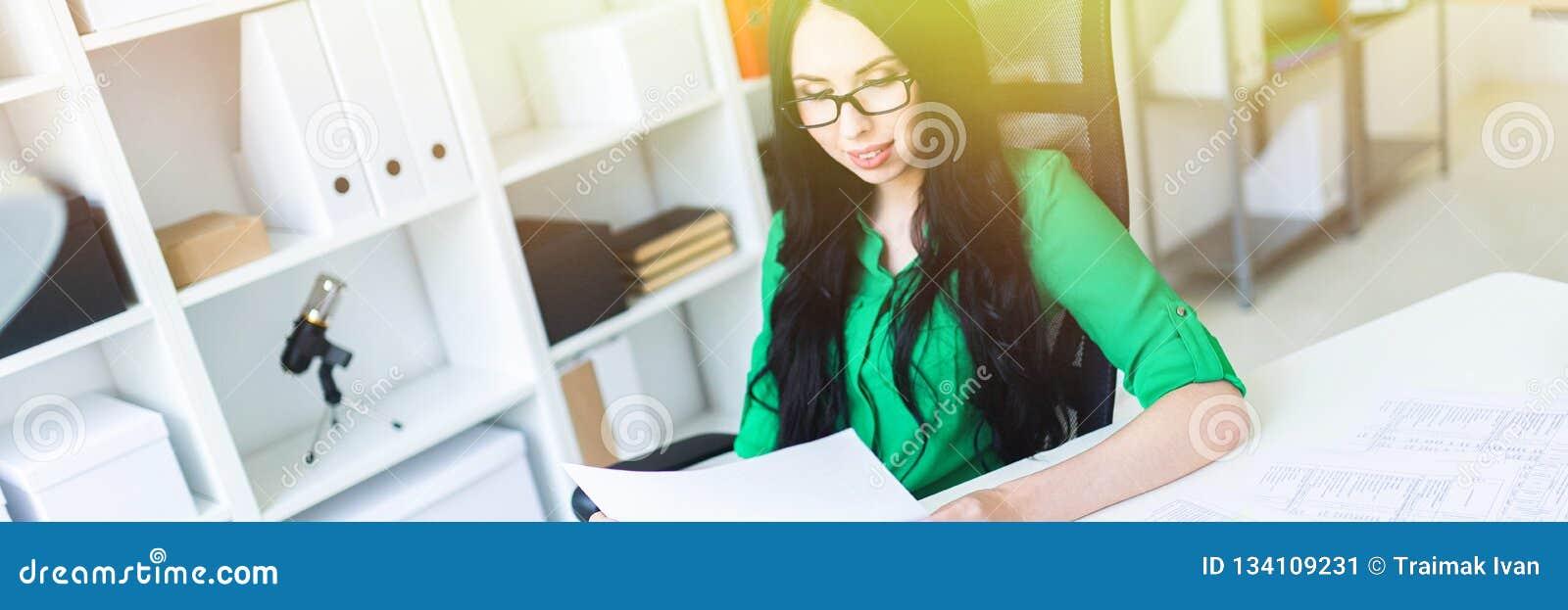 Маленькая девочка в стеклах работает в офисе с взглядами компьютера и калькулятора через документы