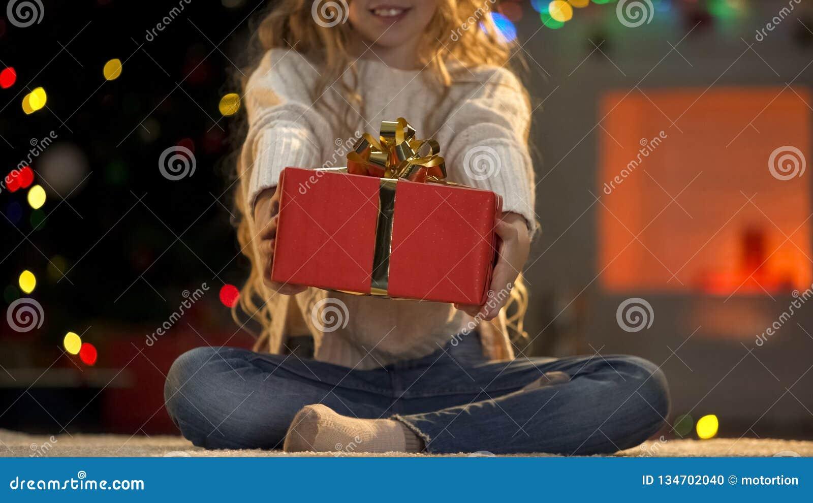 Маленькая девочка держа вне Xmas присутствующий к камере, призрению на доброжелательстве рождества