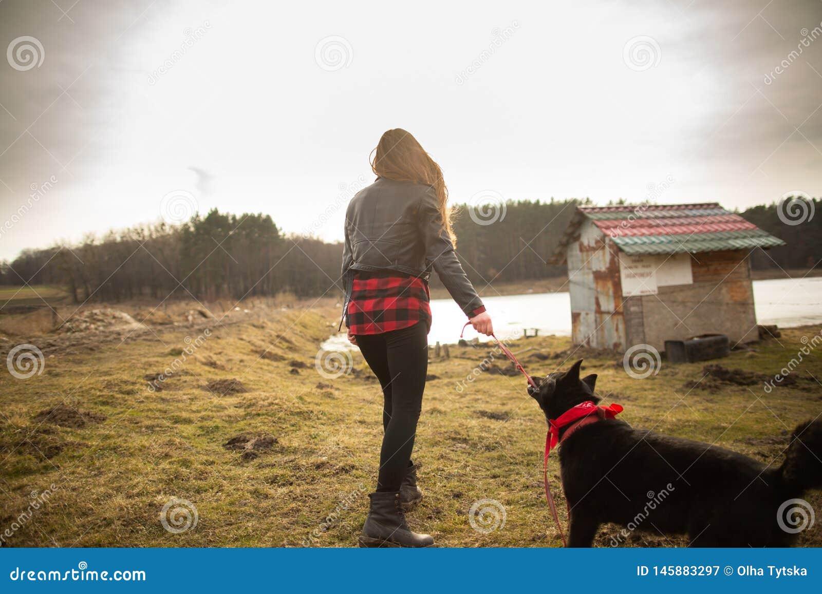 Маленькая девочка идет с ее собакой на береге озера E