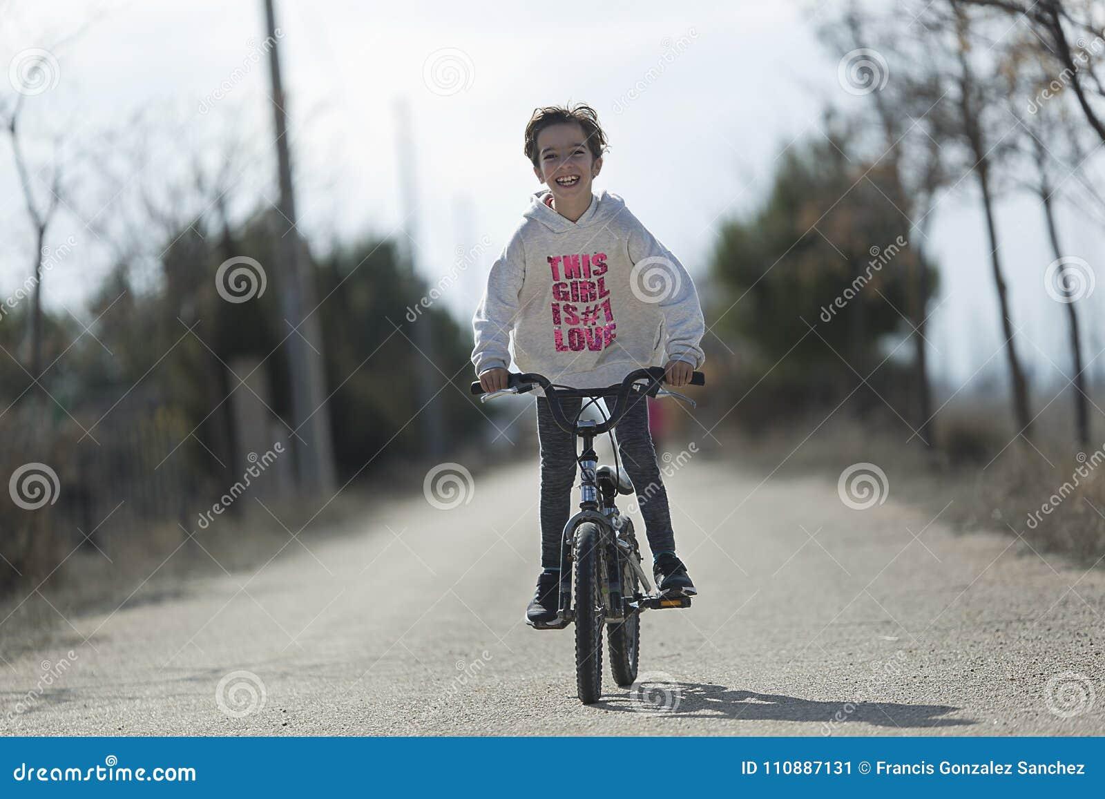 Маленькая девочка идя с ее велосипедом к усмехаться камеры
