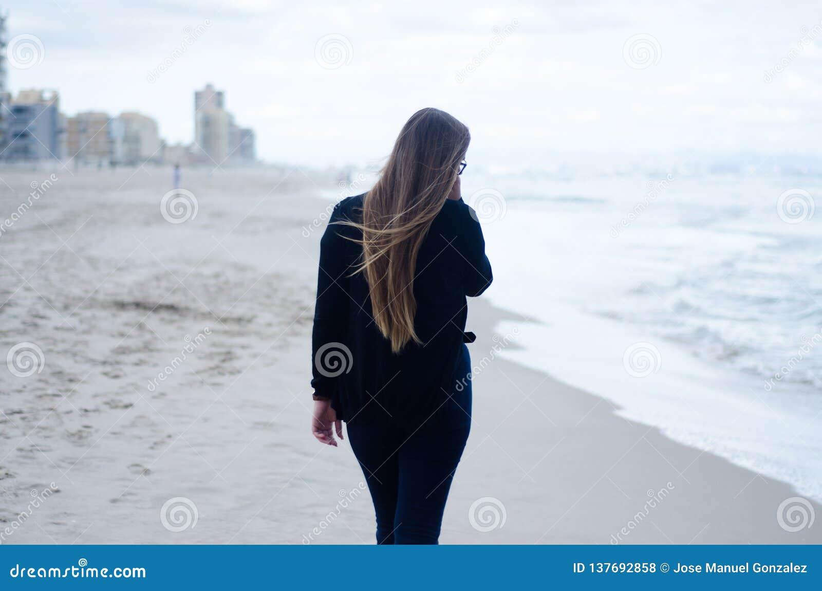 Маленькая девочка на его назад, идущ на пляж на пасмурный день