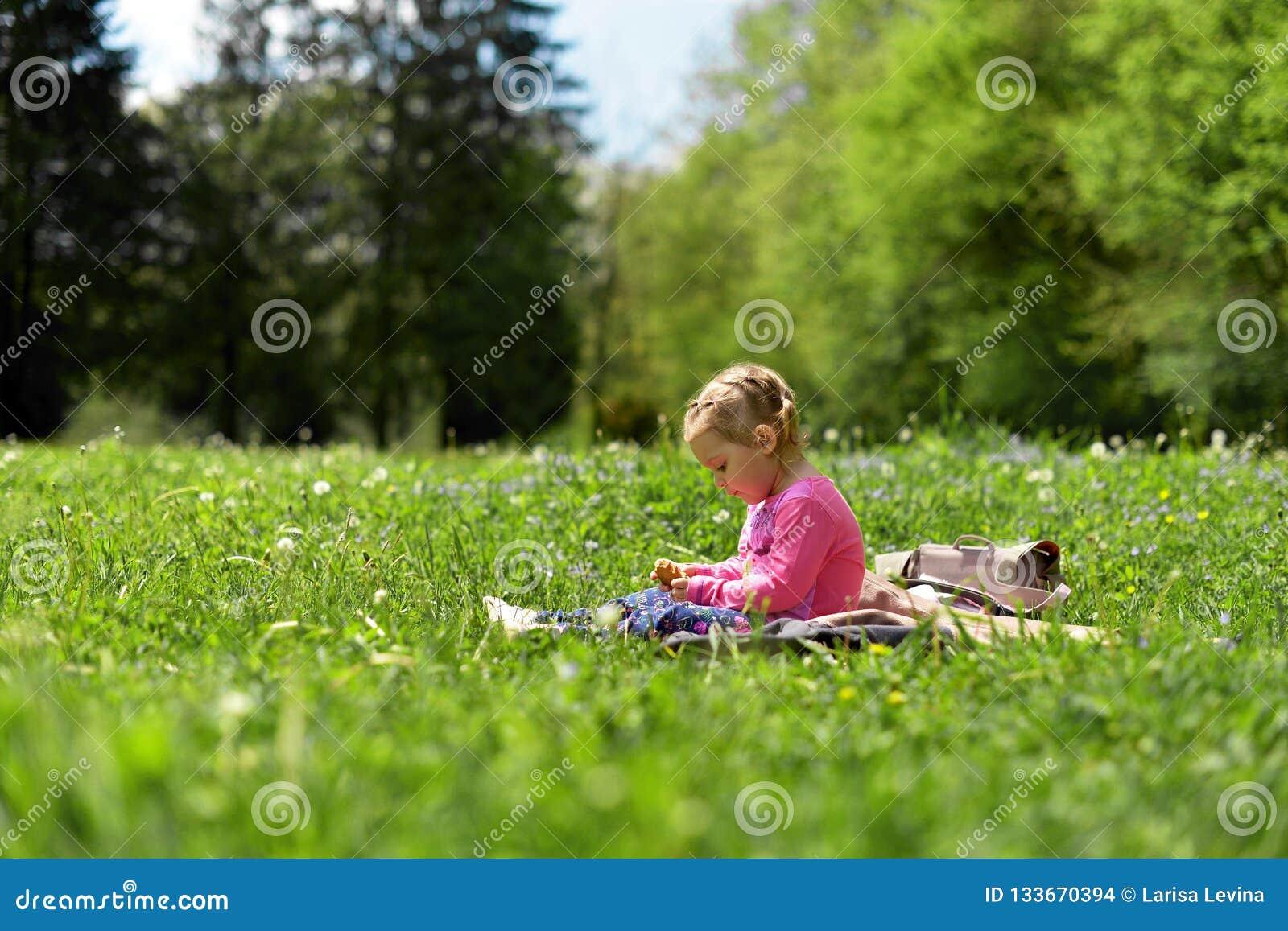 Маленькая девочка отдыхая на зеленом луге среди цветков луга