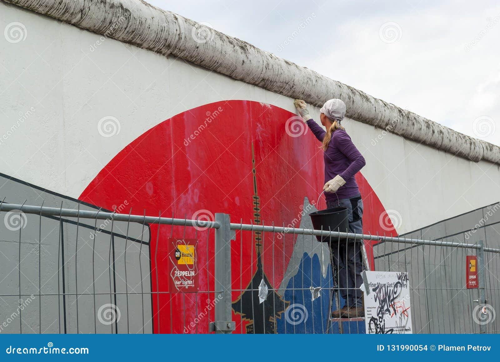 Маленькая девочка очищает Берлинскую стену, галерею Ист - Сайда, Берлин