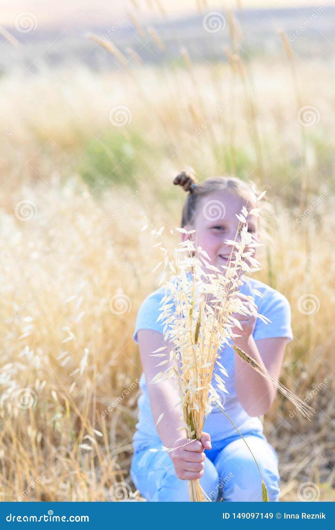 Маленькая девочка портрета прелестная, возраст 9-10 на желтом поле осени
