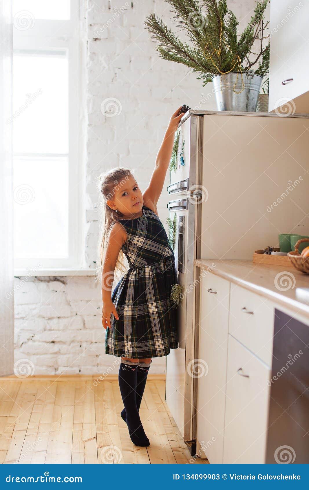 Маленькая девочка пробуя принять конус от frigde, времени рождества и украшений