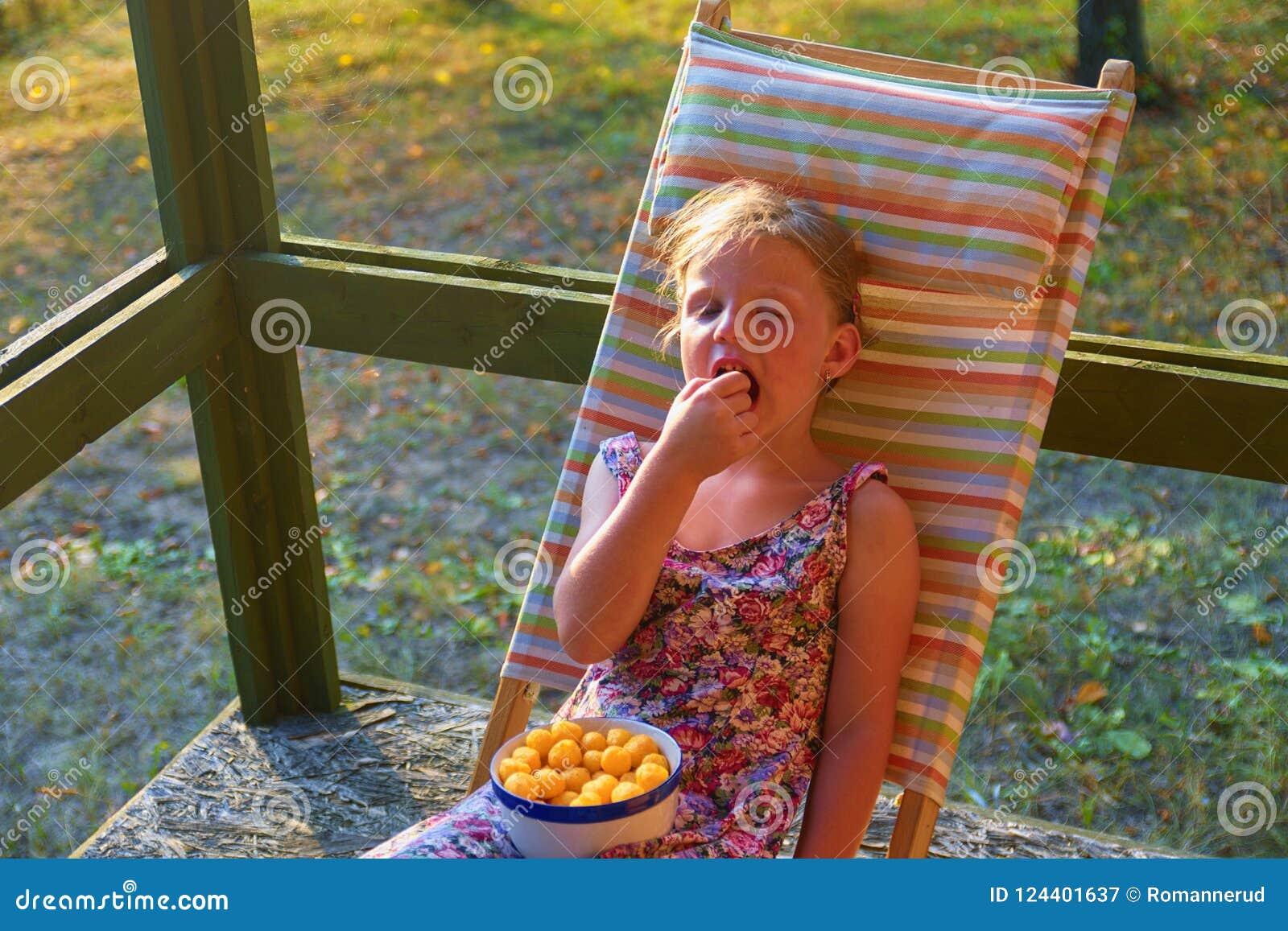 Маленькая девочка сидит на deckchair сада на verandah Малая девушка ест закуски приправленные сыром в