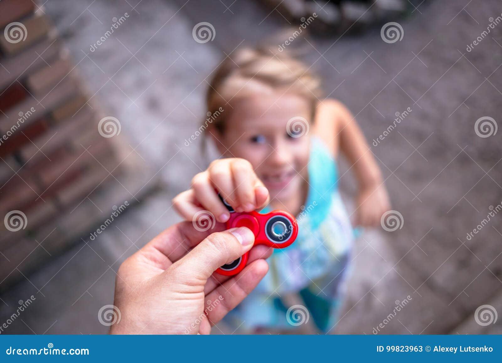 Маленькая девочка скача к руке с обтекателем втулки