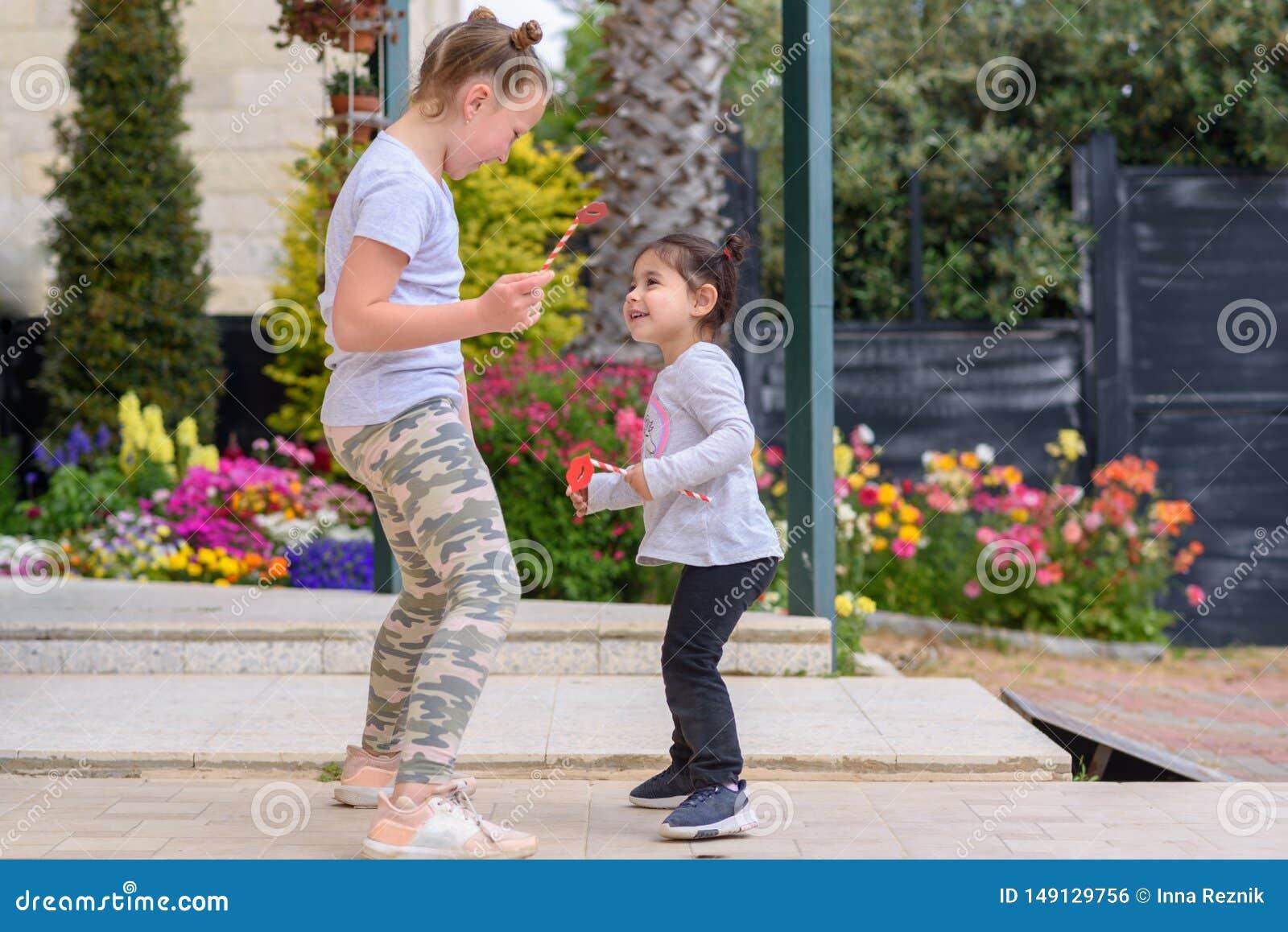 Маленькая девочка скача, танцы, имеющ потеху на открытом воздухе Счастливые летние каникулы