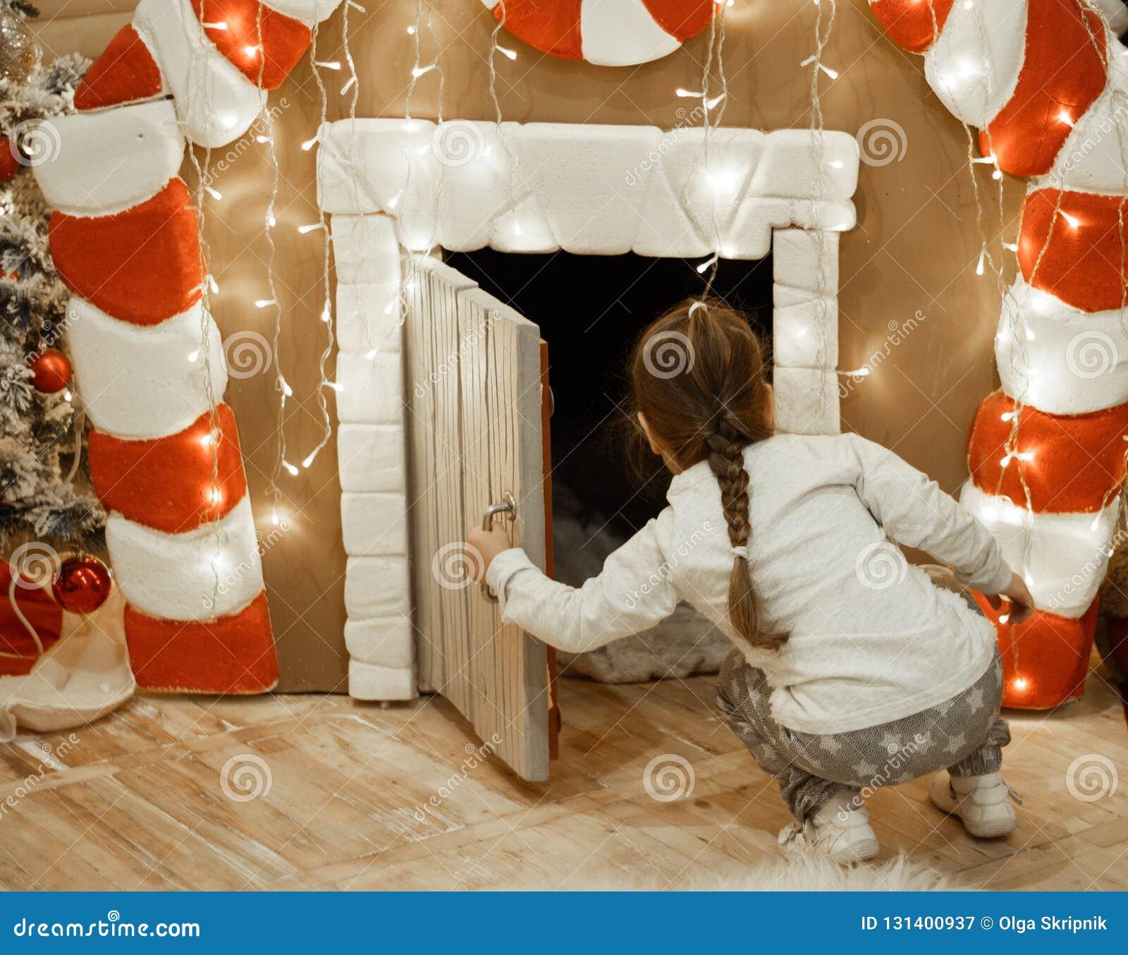 Маленькая девочка смотрит в доме пряника, оформлении Нового Года, около светов и рождественской елки