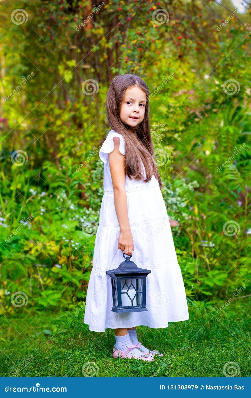 Маленькая девочка стоит в саде и держит фонарик