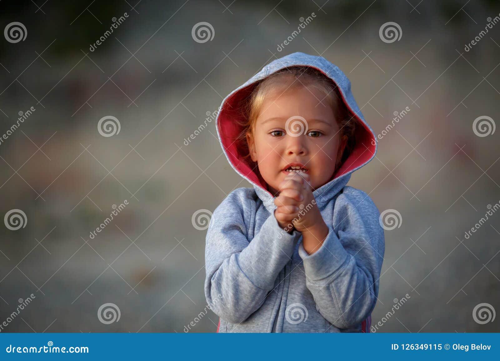 Маленькая девочка стоит при ее сжиманные руки и умоляет для того чтобы выполнить ее желание