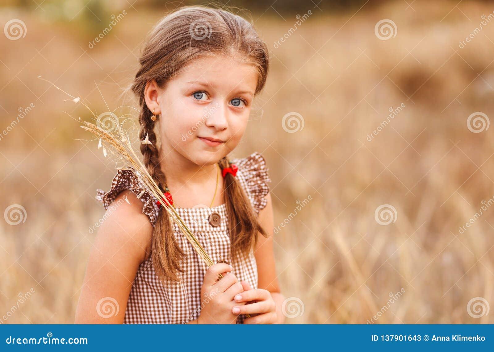 Маленькая девочка с большими глазами на пшеничном поле держа букет трав