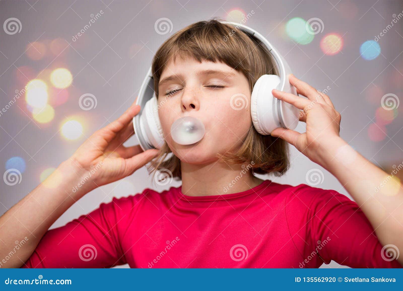 Маленькая девочка с жевательной резиной наушников на белизне