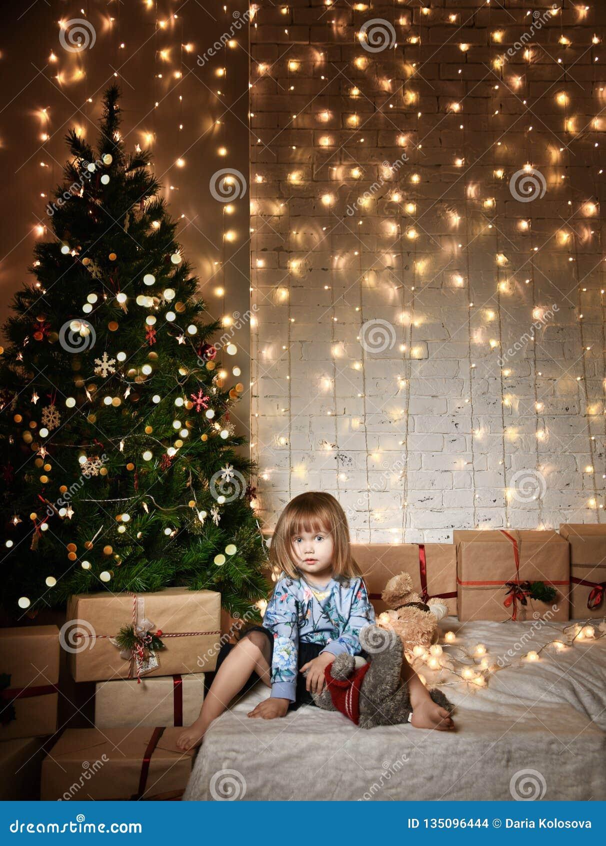 Маленькая девочка с подарками рождества около рождественской елки