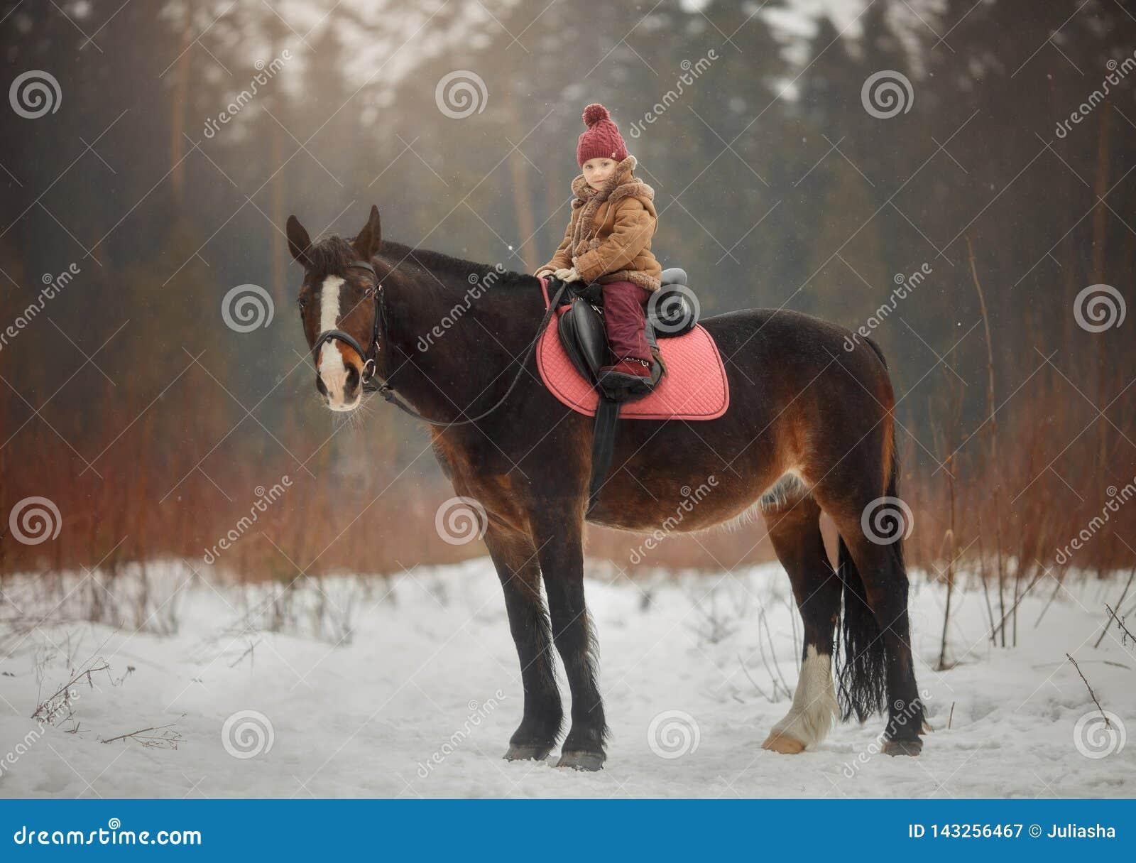 Маленькая девочка с портретом лошади на открытом воздухе на весеннем дне