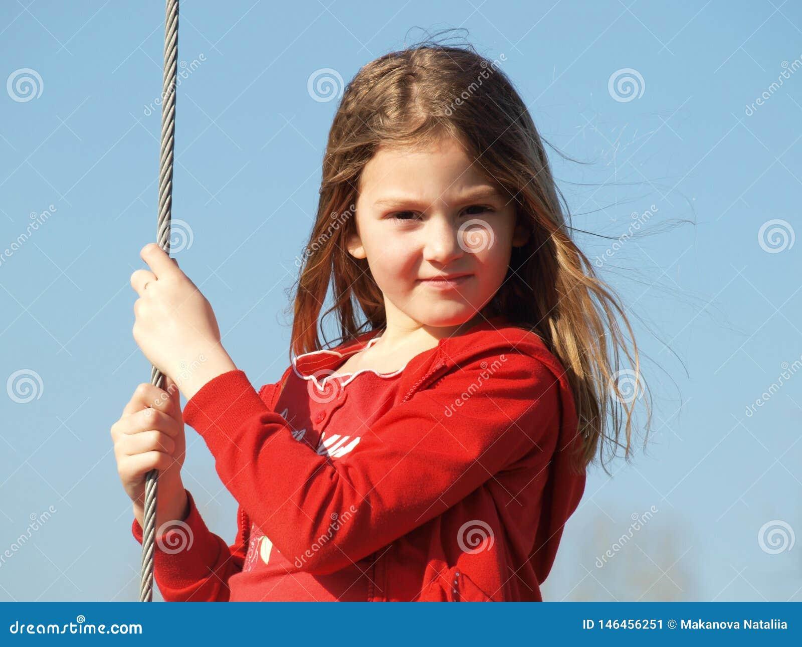 Маленькая девочка с пропуская светлыми волосами в красном свитере против голубого неба