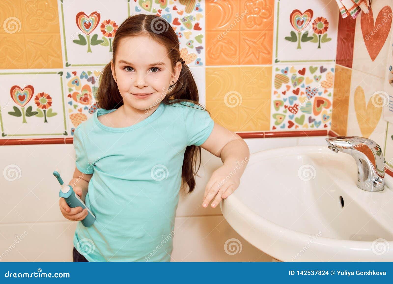 Маленькая девочка чистя ее зубы щеткой в ванной комнате