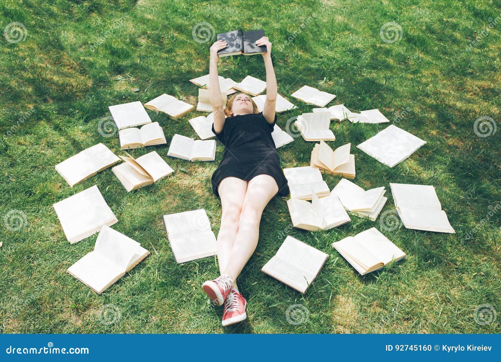 Маленькая девочка читая книгу пока лежащ в траве Девушка среди книг в саде лета