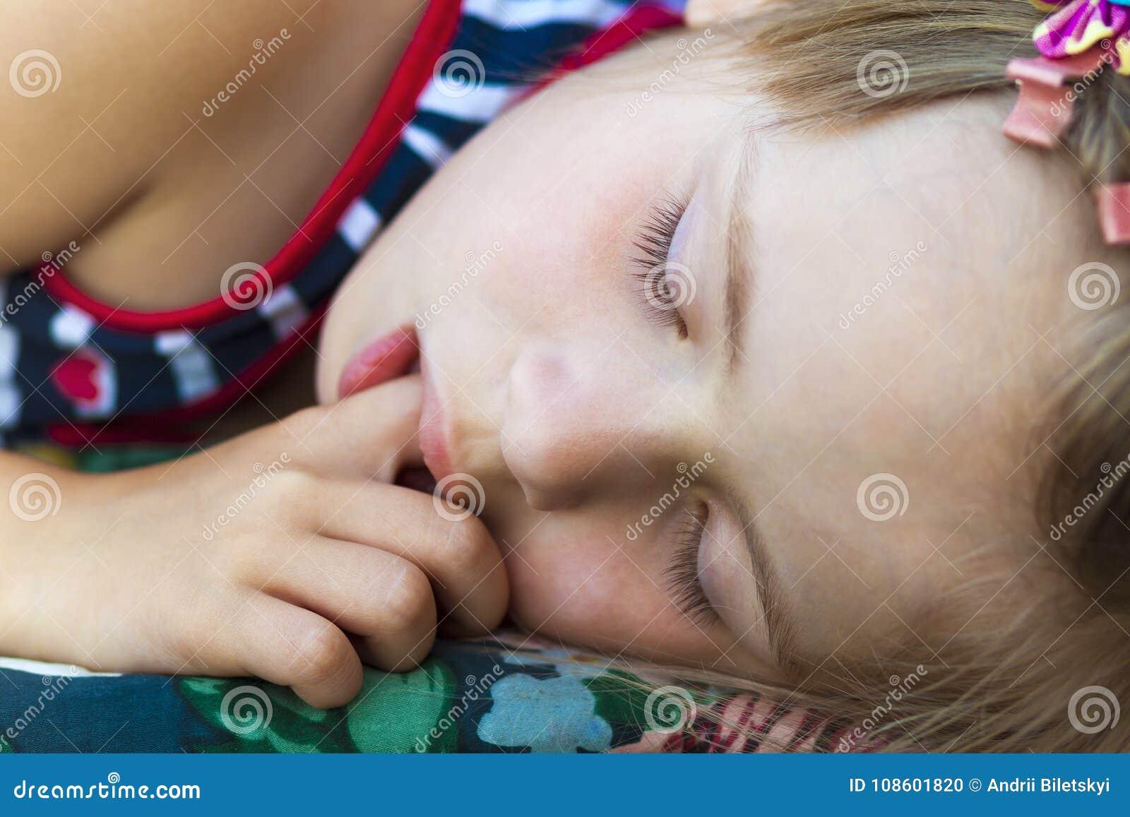 Маленькая милая девушка спать, всасывая большой палец руки и имея сладостное drea