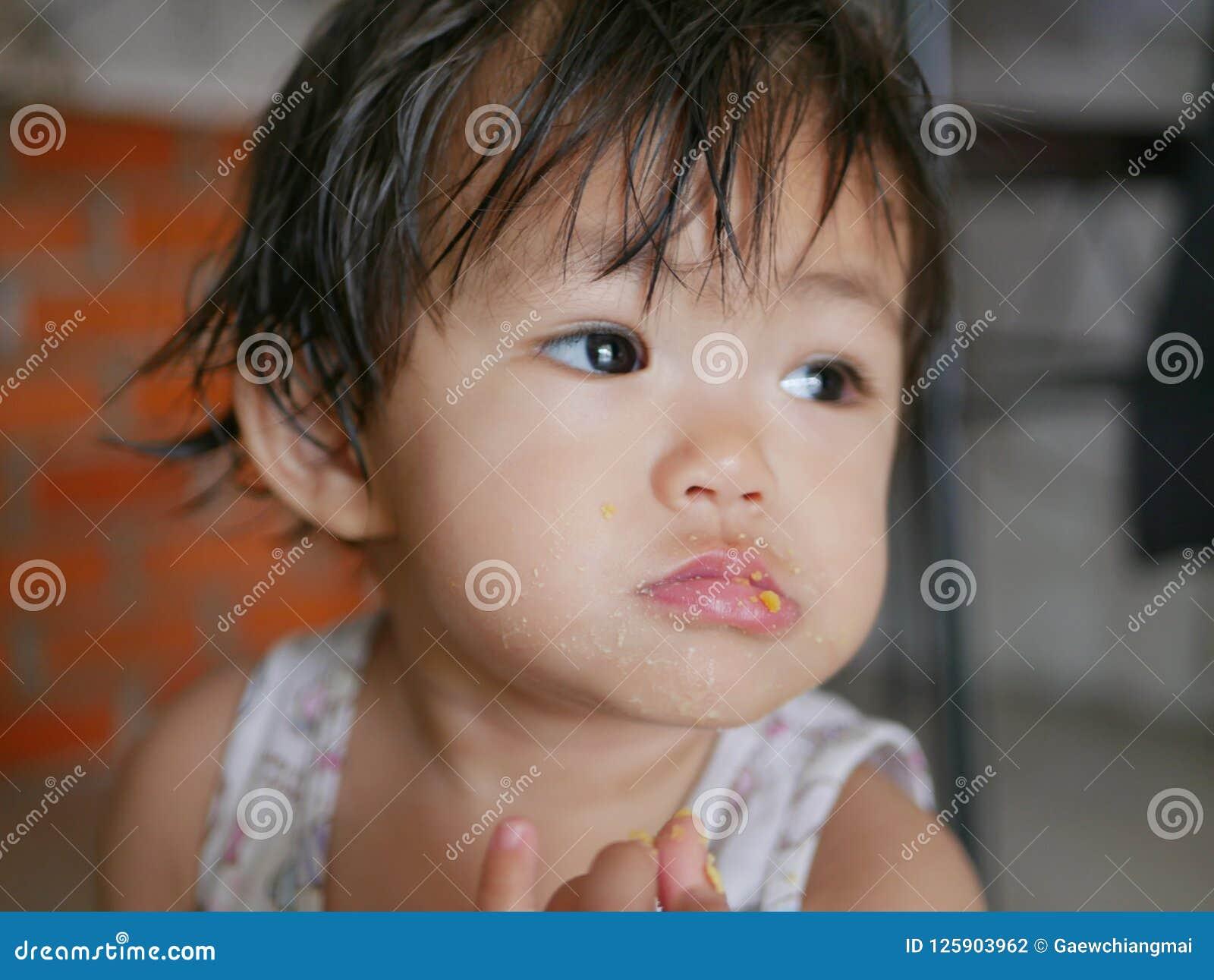 Маленькие азиатские губы ребёнка покрытые с яичком пока она учит съесть вареное яйцо сама
