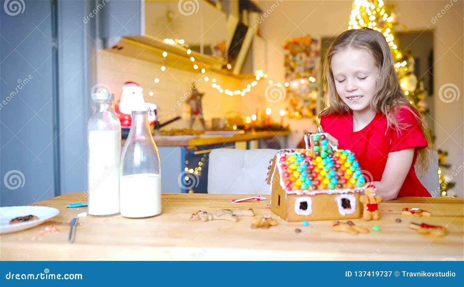 Маленькие девочки делая дом пряника рождества на камине в украшенной живущей комнате видеоматериал