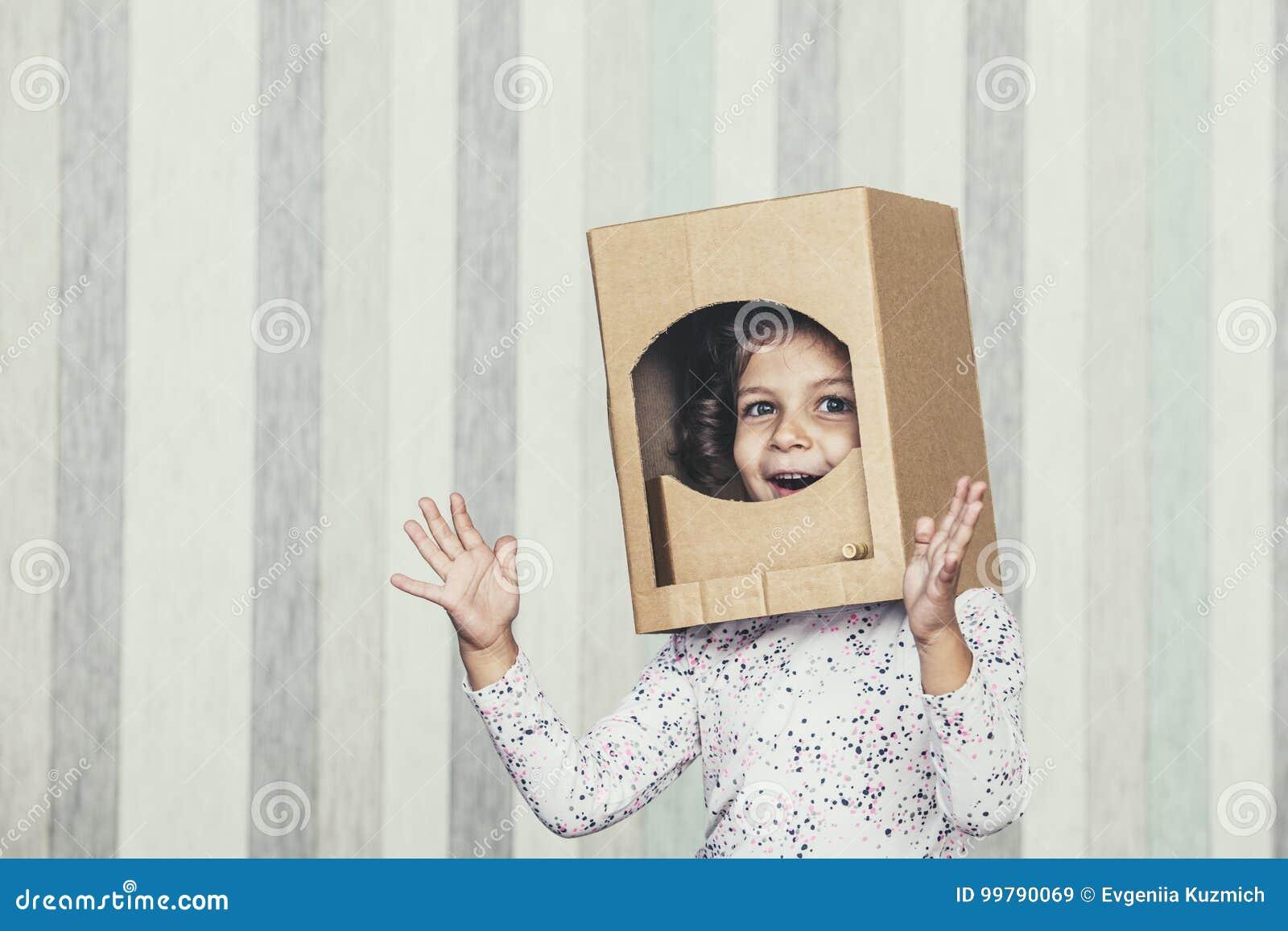 Маленькие девочки ребенка играя астронавта в portr шлема картона