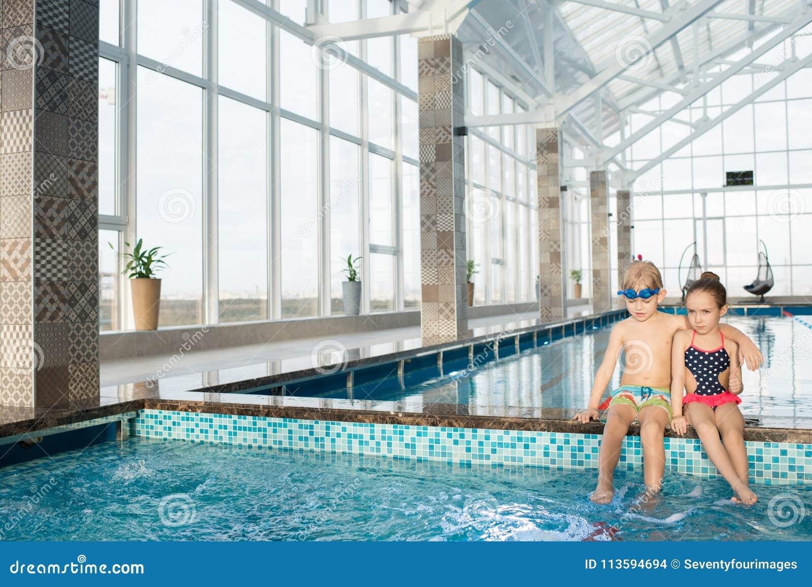 Маленькие друзья отбрасывая ноги в бассейне