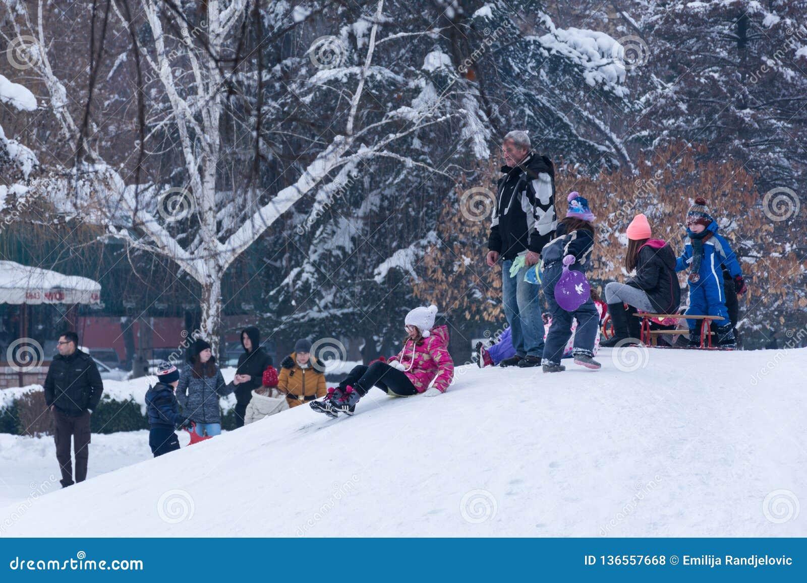 Маленькие ребята и люди наслаждаясь на снеге и sledding вниз с холмов