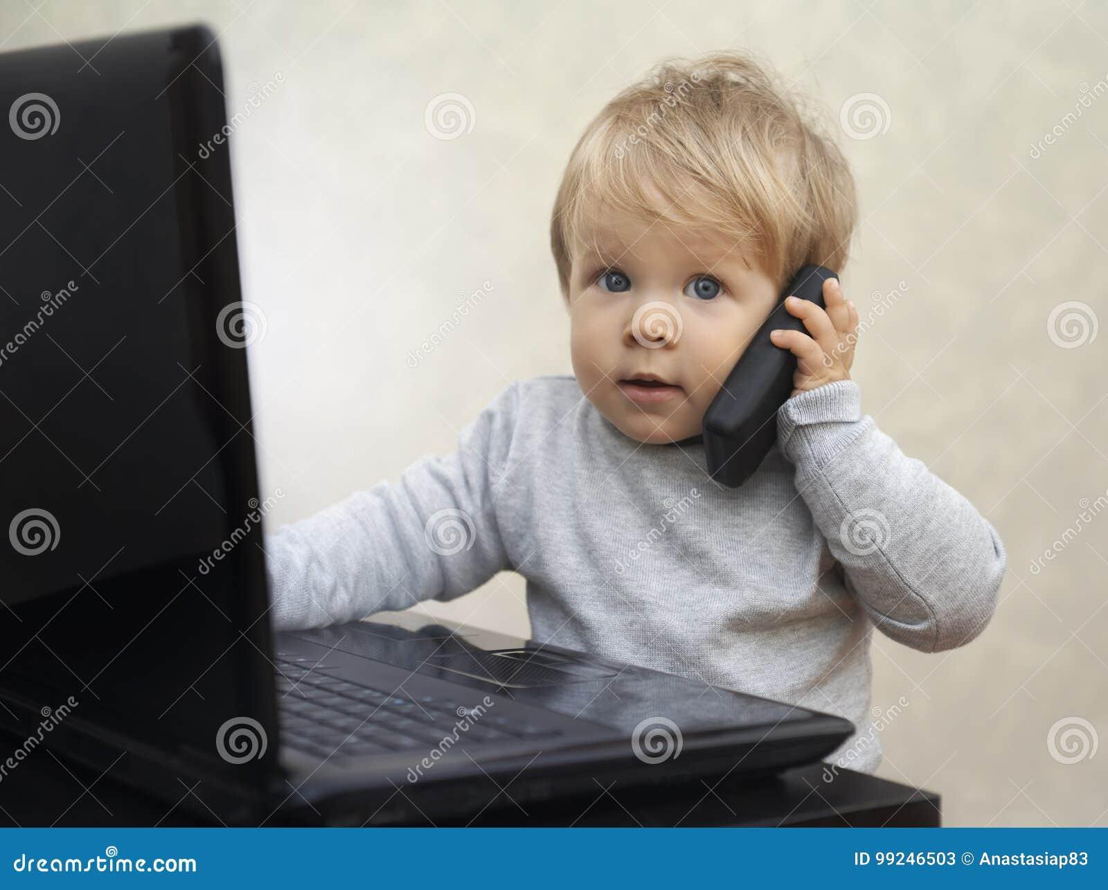 Маленький бизнесмен сидя на компьютере с сотовым телефоном игрушки