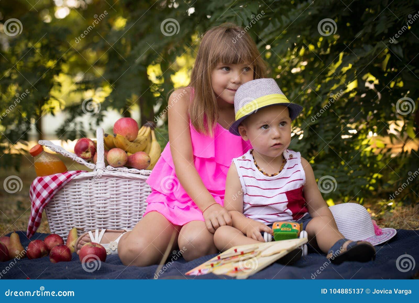 Маленький брат и сестра сидя на траве в парке близко